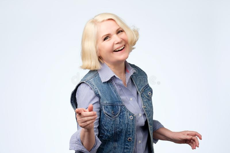 Mature woman pointing finger and toothy smile. Studio shot. Mock or bad joke concept. Mature woman pointing finger and toothy smile. Studio shot stock images