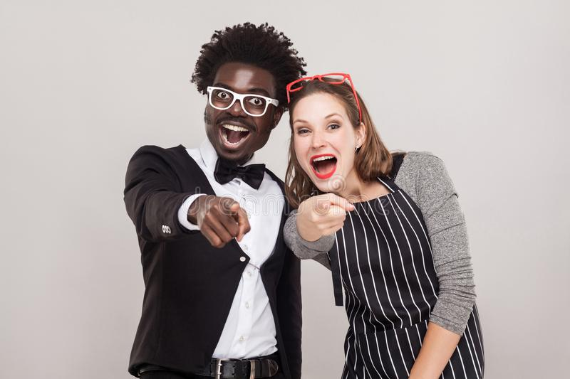 Mock, sneer concept. Colorful couple pointing fingers at camera. And smiling. Studio shot, gray background stock photo
