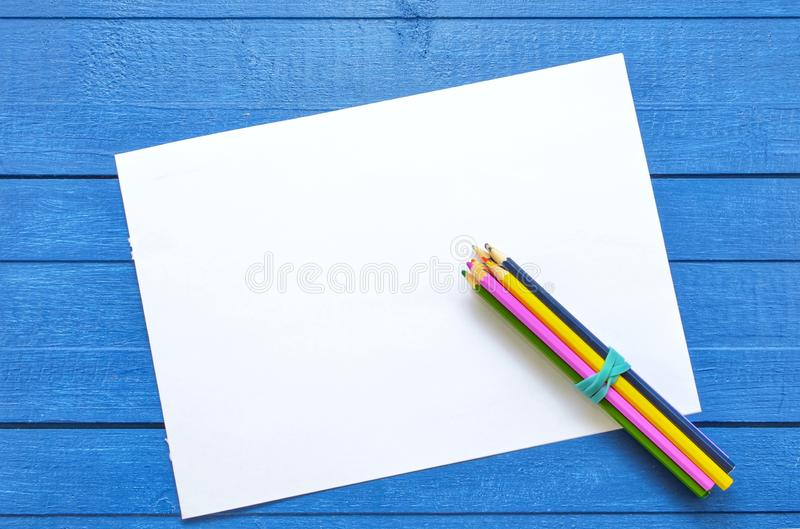 Mock up artwork for drawing and text on a blue wooden background with four colored pencils on the corner of empty sheet. Flat lay.Creativity concept stock photos