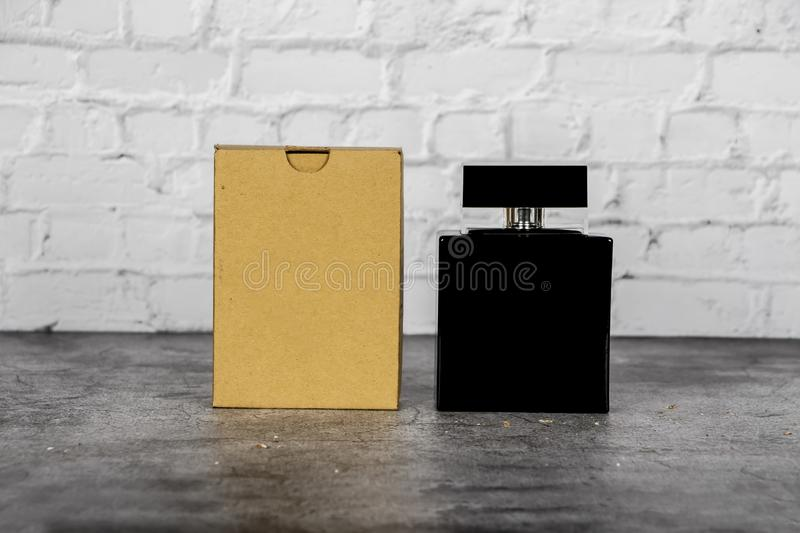 Mock up of a black bottle of men`s perfume on a brick gray wall background. Place for text. Mock up of a black bottle of men`s perfume on a brick gray wall stock photo