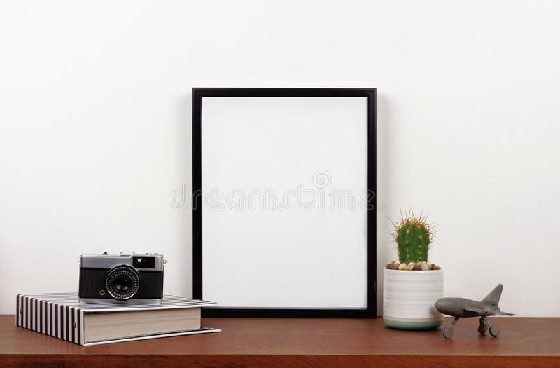 Mock up black frame against white wall with travel decor on a wood shelf royalty free stock images