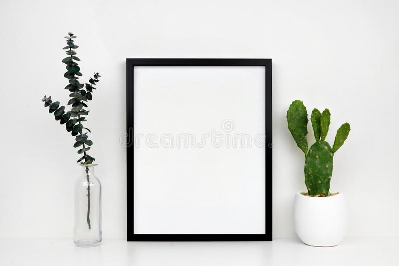 Mock up black frame with cactus and branches on a white shelf or desk against a white wall royalty free stock photo