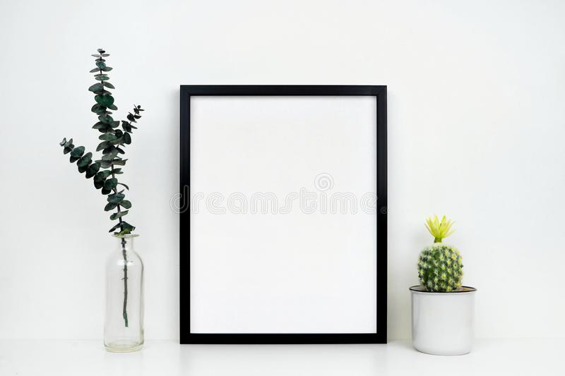 Mock up black frame with cactus and branches on a white shelf or desk against a white wall royalty free stock images