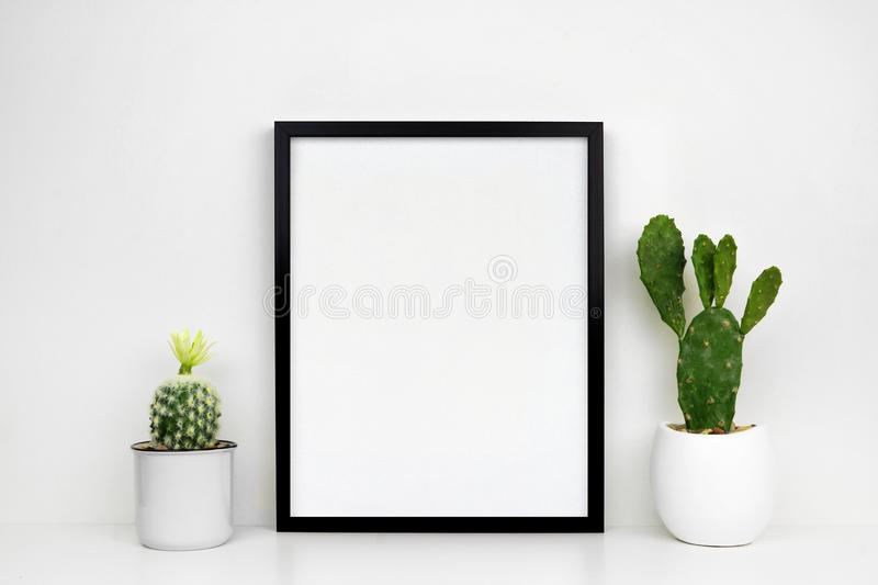 Mock up black frame with cactus plants on a white shelf or desk against a white wall stock images
