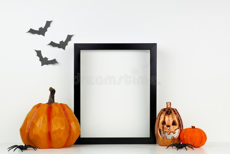 Mock up black frame with Halloween Jack o Lantern and pumpkin decor on a shelf against a white wall. Mock up black frame with Jack o Lantern and pumpkin decor on stock photo