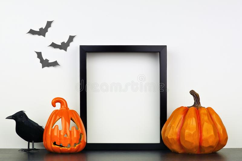 Mock up black frame with Halloween Jack o Lantern, pumpkin and crow decor on a shelf against a white wall stock image