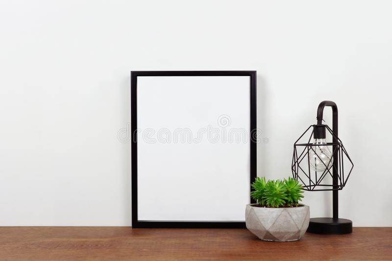 Mock up black frame against white wall with plant and lamp on a wood shelf stock photos