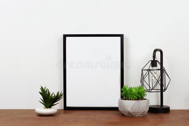 Mock up black frame against white wall with succulent plants and lamp on a wood shelf royalty free stock images