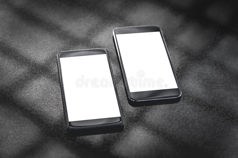 Mock up of black smartphones on a gray background with the shadow of the lattice. royalty free stock image