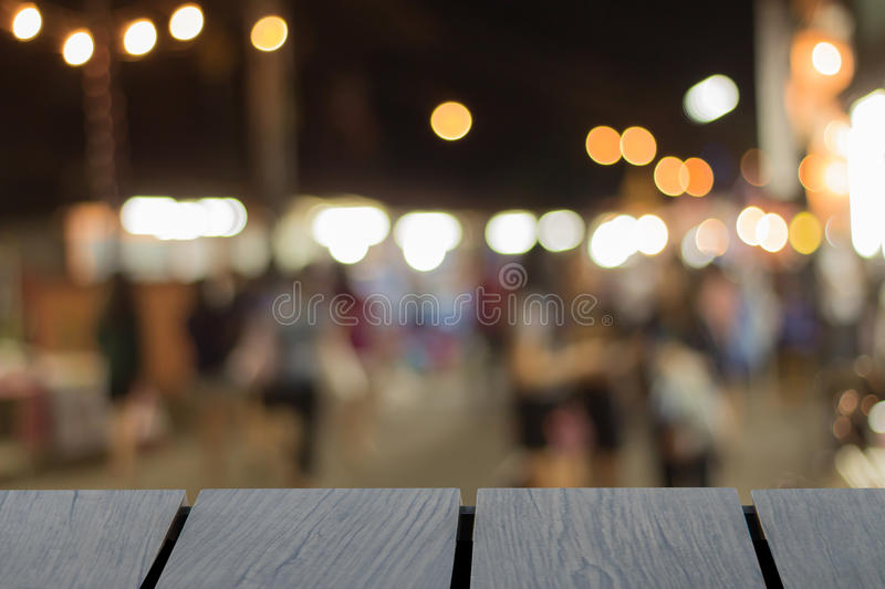 Mock up black wooden table font and blurred walking street background. Blur people stock image