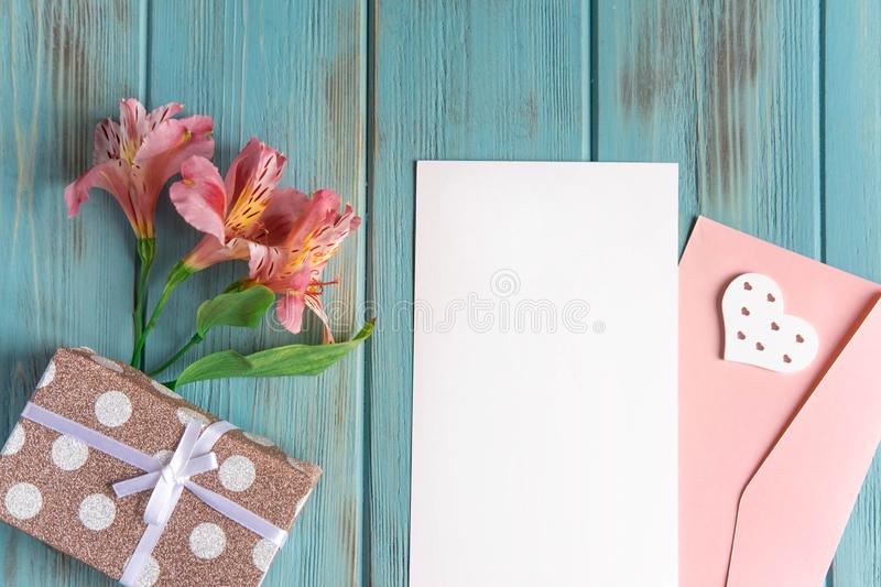 Mock up blank paper and envelope on blue wooden background with natural flowers of pink color. Blank, frame for text. Greeting card design with flowers stock photography