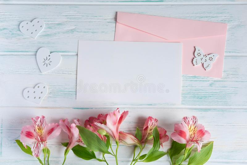 Mock up blank paper and envelope on white wooden background with natural flowers of pink color. Blank, frame for text. Greeting. Card design with flowers royalty free stock images