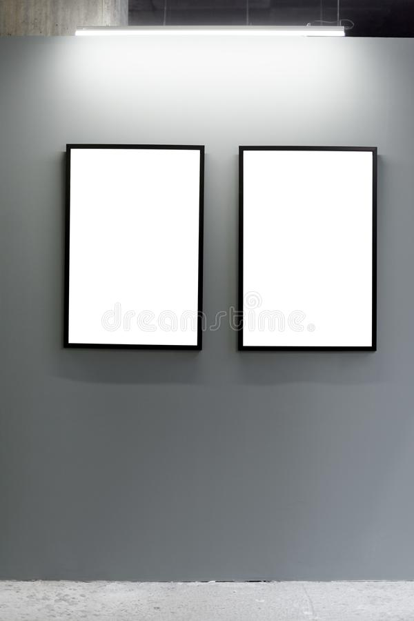 Mock up. Blank picture frames on gray wall in the loft interior. Gallery wall with empty poster frames indoor. Mock up. Blank picture frames on gray wall in the stock photography