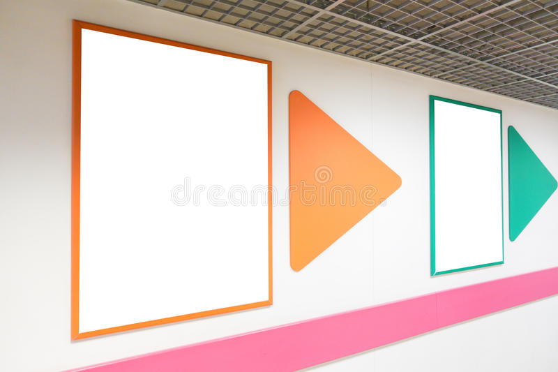 Mock up blank poster frames with colorful frames hanging on wall in shopping mill. Mock up blank advertising poster frame with colorful frames hanging on wall in stock photos