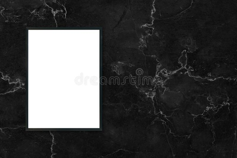 Mock up blank poster picture frame hanging on black marble wall background in room. Mock up blank poster picture frame hanging on black marble wall background stock photo