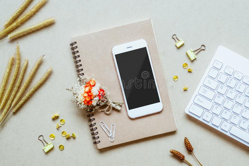 Mock up blank screen mobile phone on home office desk. Office desk table with supplies. Flat lay Business workplace and grass stock photo
