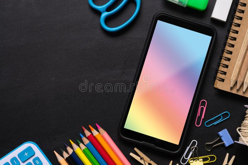 Mock up blank screen mobile phone and mix of office supplies background. Stationery items background with copy space, top view royalty free stock photography