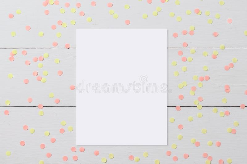 Mock-up of blank white card on light wooden background with confetti, funny desktop for any holiday stock image