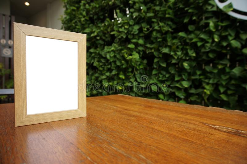 Mock up Blank white frame standing on wood table in Bar restaurant cafe. space for text. product display montage. stock image