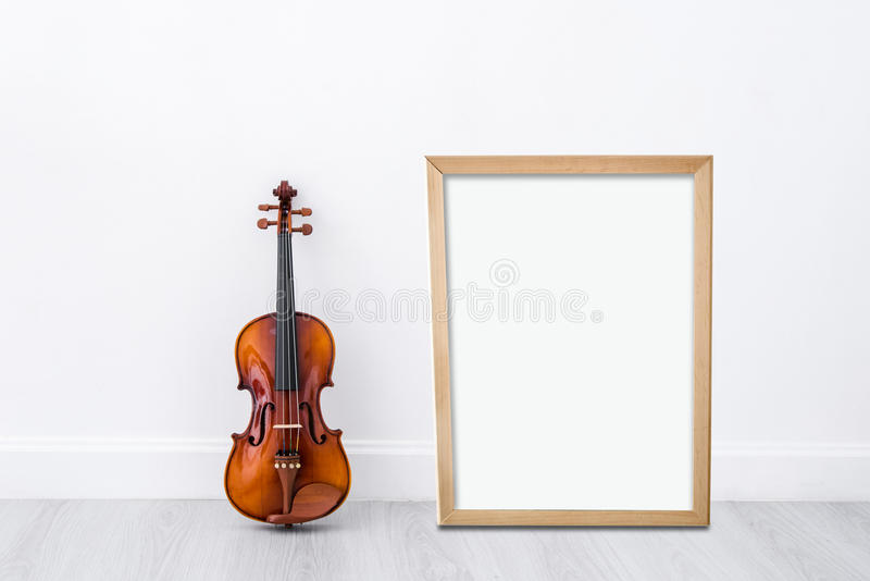 Mock up blank wooden frame board. For display with Classical cello on white wall background stock photos