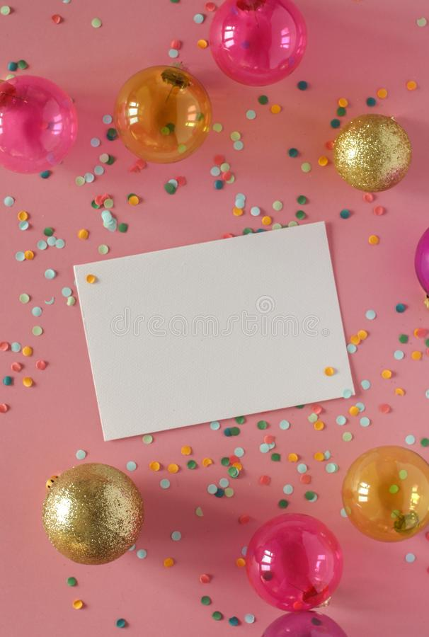 Mockup card on a pink background with their Christmas decorations and confetti. Invitation, card, paper. Place for text. Mock up card on pink background with stock photography