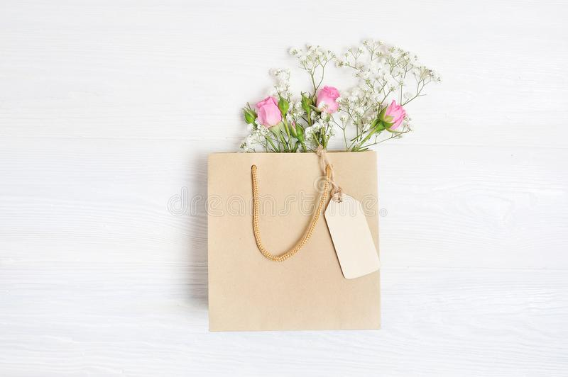 Mock up Composition paper bag and tag of white flowers rustic style, for St. Valentine`s Day with a place for your text. Flat lay, top view photo mock up stock images