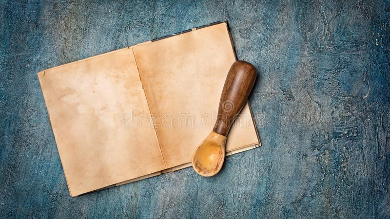 Mock up of empty old vintage cookbook with yellowed paper pages and rustic spoon. Mockup of empty old vintage cookbook with yellowed paper sheets and wooden stock image