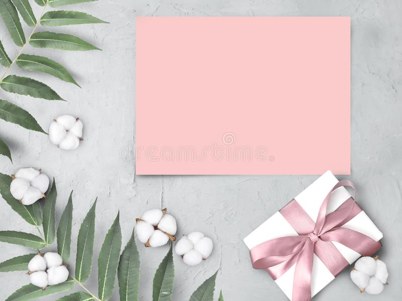 Mock up empty pink paper blank with gift box,  cotton flowers and leaves on grey textured  background. stock images