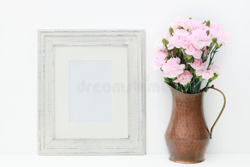 Download A Mock Up Of A Empty White Frame And Flowers. Stock Photo - Image: 80170804