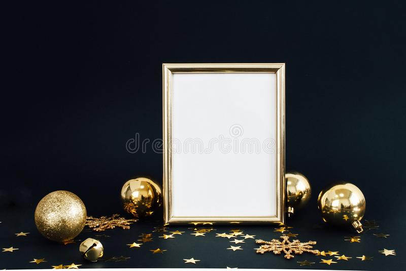 Mock up frame on dark background with Christmas decorations glitter snowflakes, baubles, bell and stars confetti. Invitation, card. Paper. Place for text stock photos