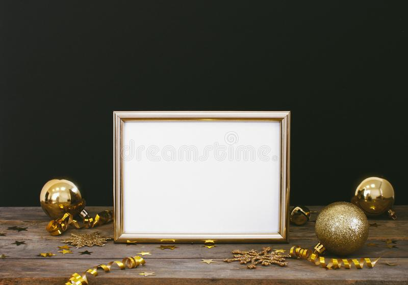 Mock up frame on wood rustic dark background with Christmas decorations glitter snowflakes, baubles, bell, serpentine and stars co. Nfetti. Invitation, card royalty free stock photo