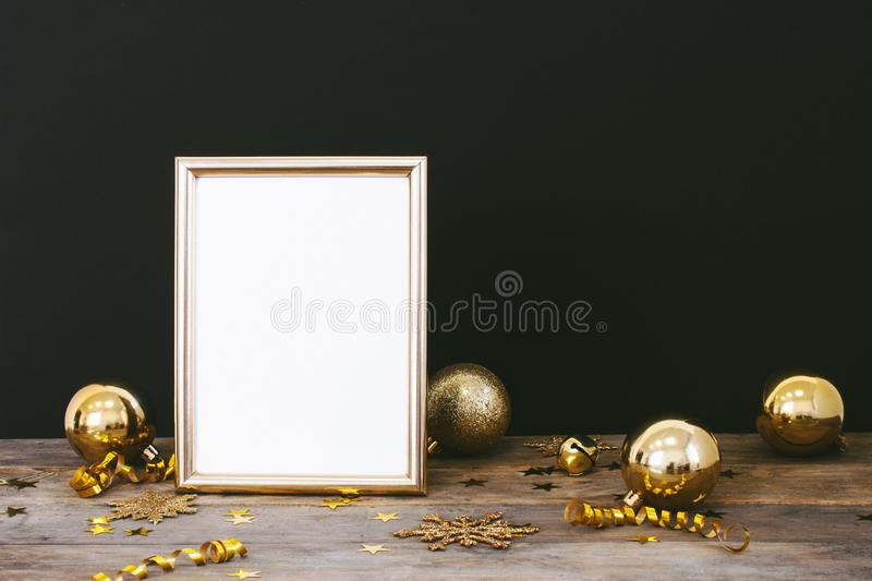 Mock up frame on wood rustic dark background with Christmas decorations glitter snowflakes, baubles, bell, serpentine and stars co. Nfetti. Invitation, card royalty free stock photography