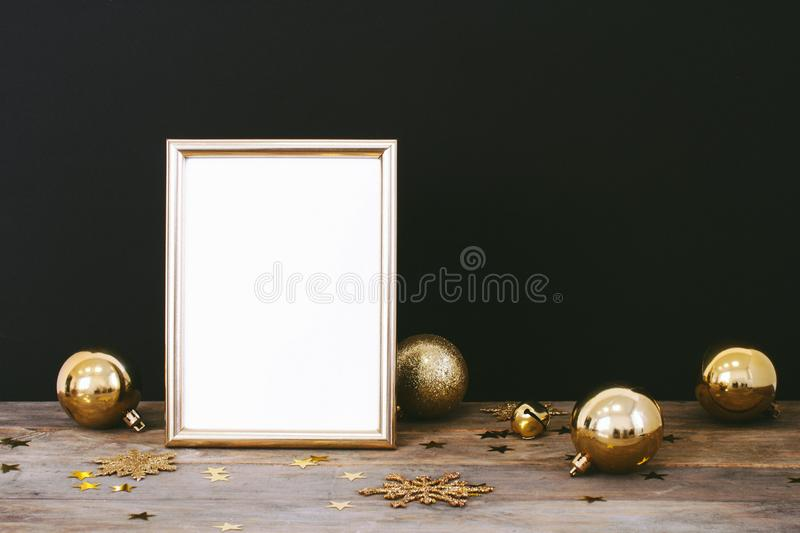 Mock up frame on wood rustic dark background with Christmas decorations glitter snowflakes, baubles, bell and stars confetti. Invi stock photo