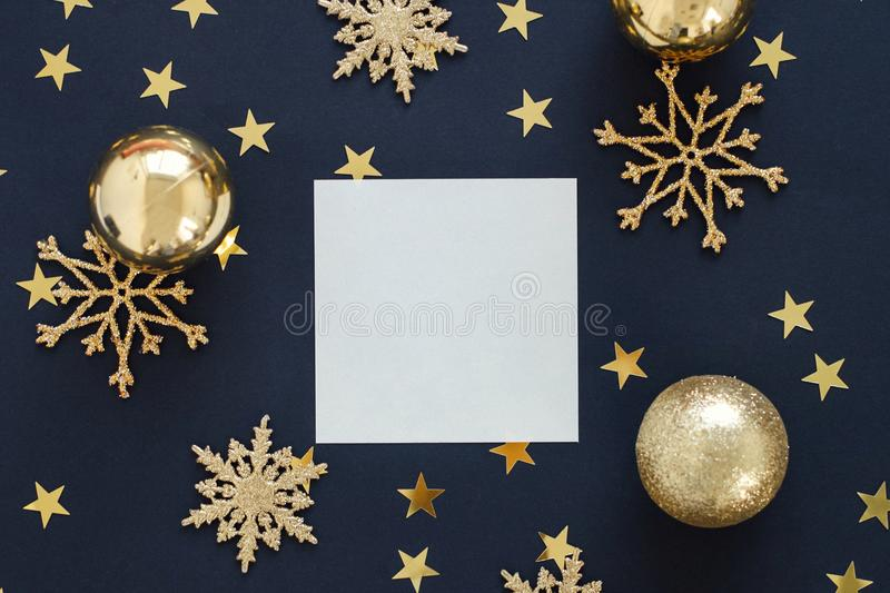 Mock up greeting card on black background with Christmas decorations ornaments glitter snowflakes, baubles and gold stars confetti. Mock up greeteng card on royalty free stock photo