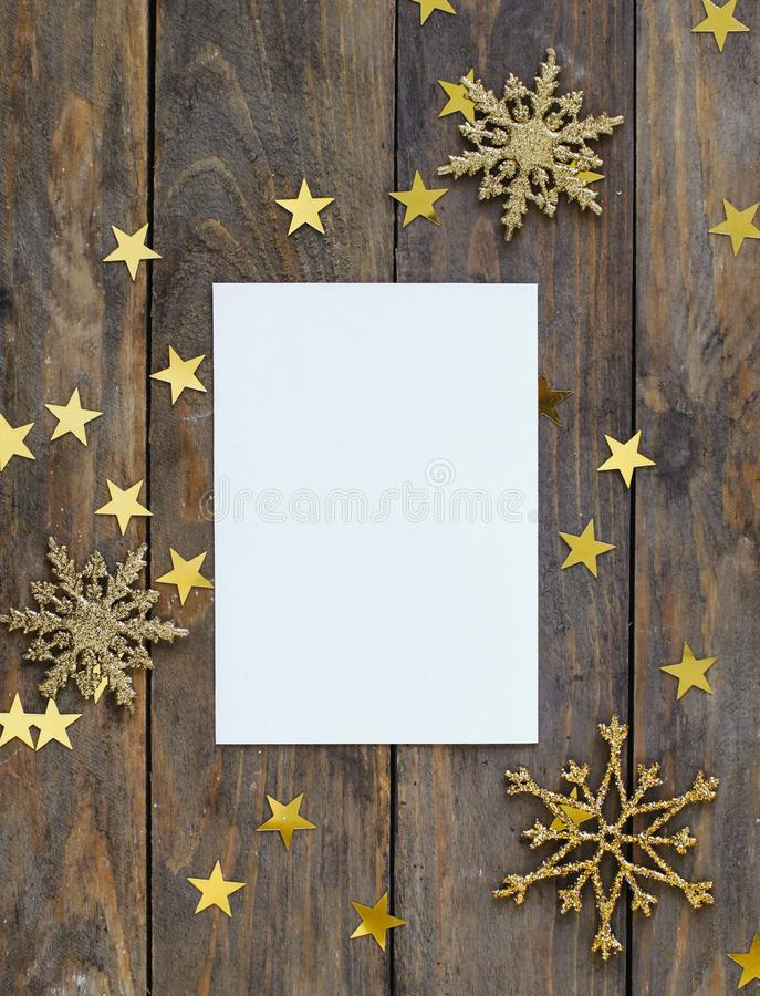 Mock up greeteng card on wood rustic background with Christmas decorations glitter snowflakes and gold stars confetti. Invitation,. Paper. Place for text flat stock photos