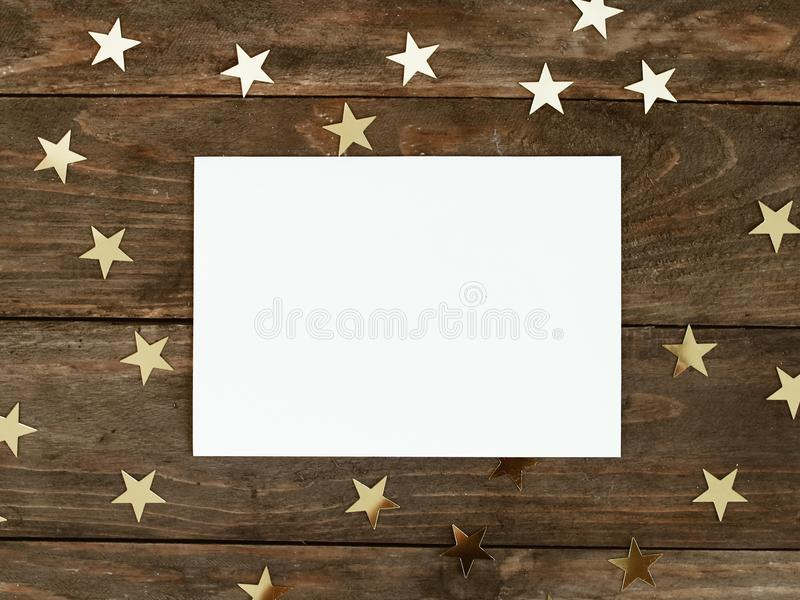 Mock up greeting card on wood rustic background with Christmas gold stars confetti. Invitation, paper. Place for text flat lay stock photo
