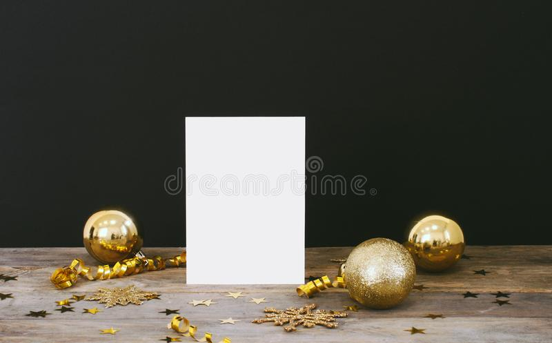 Mock up greeteng card on wood rustic dark background with Christmas decorations glitter snowflakes, baubles, bell, serpentine and. Stars confetti. Invitation royalty free stock images
