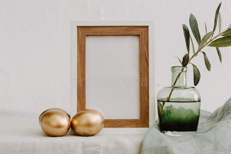Mock Up Happy Easter. Gold eggs, frame and olive brunch royalty free stock images