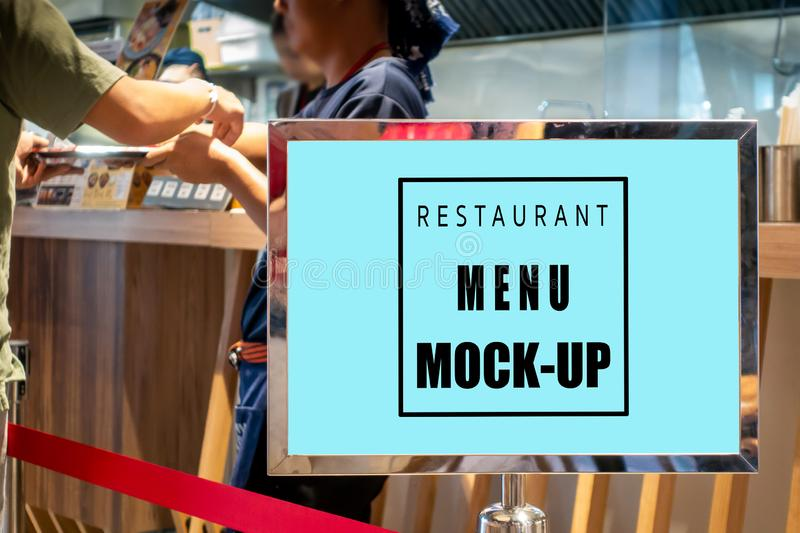 Mock up horizontal signboard in metal frame at restaurant. Mock up perspective blank horizontal signboard in metal frame with clipping path standing near counter stock image