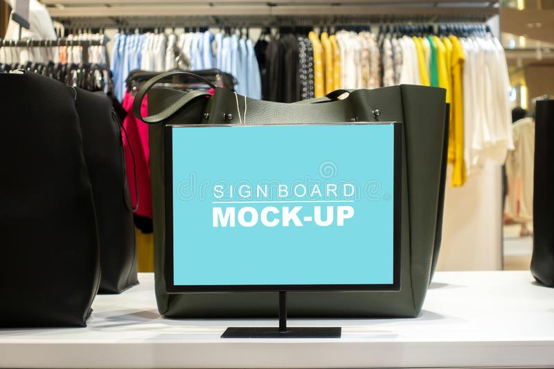 Mock up horizontal signboard show promotion in fashion shop. Mock up horizontal blank signboard with clipping path in acrylic stand on table to show price or stock image