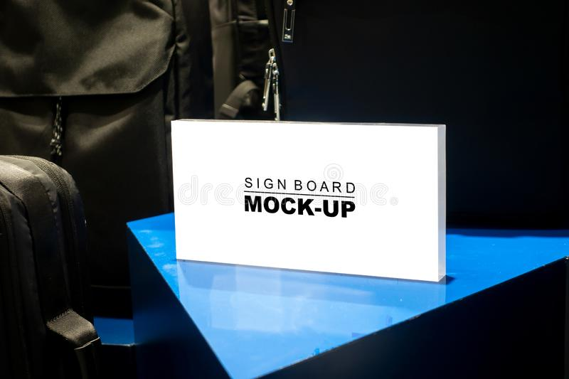 Mock up horizontal signboard show promotion in fashion shop. Mock up blank signboard with clipping path in acrylic stand on table to show price or promotion royalty free stock photography