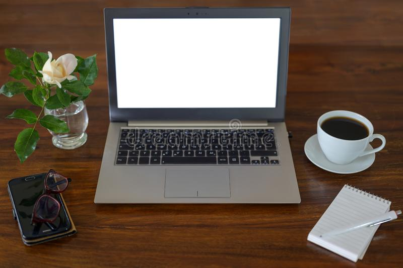 Mock up, laptop with blank white screen on a wooden desk with notepad, glasses, coffee cup, phone and a flower, business workspace stock images