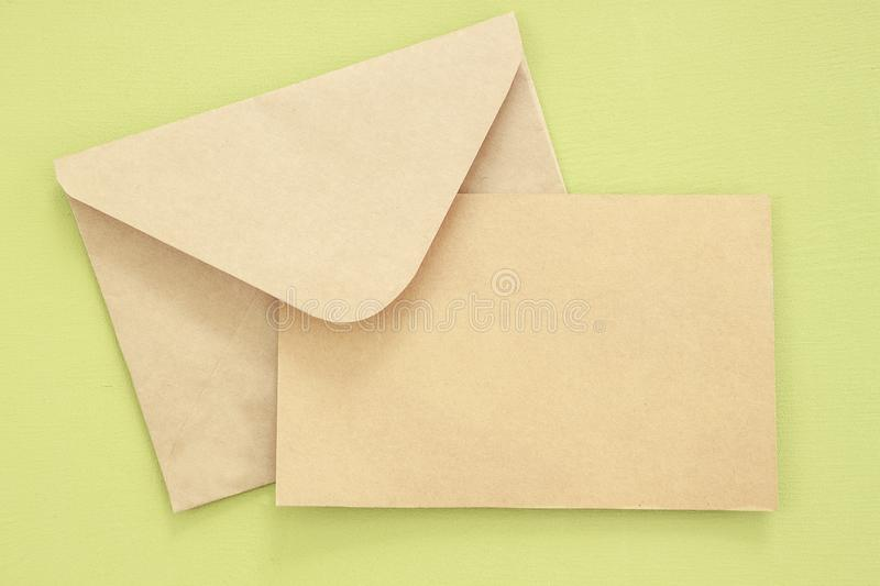 Mock-up letter or postcard with envelope on green background royalty free stock image