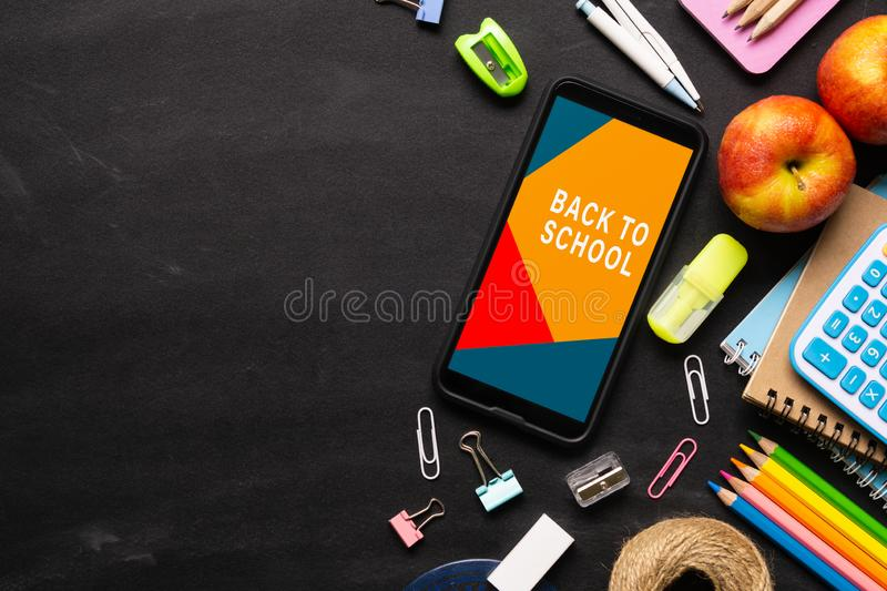 Mock up mobile phone for back to school background concept. School items on black chalkboard background with copy space, top view royalty free stock photos