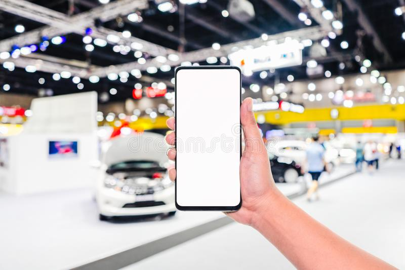 Mock up mobile phone. Hand holding mobile phone with abstract blurred cars exhibition show background image. Car shopping online,. Internet and social network royalty free stock image