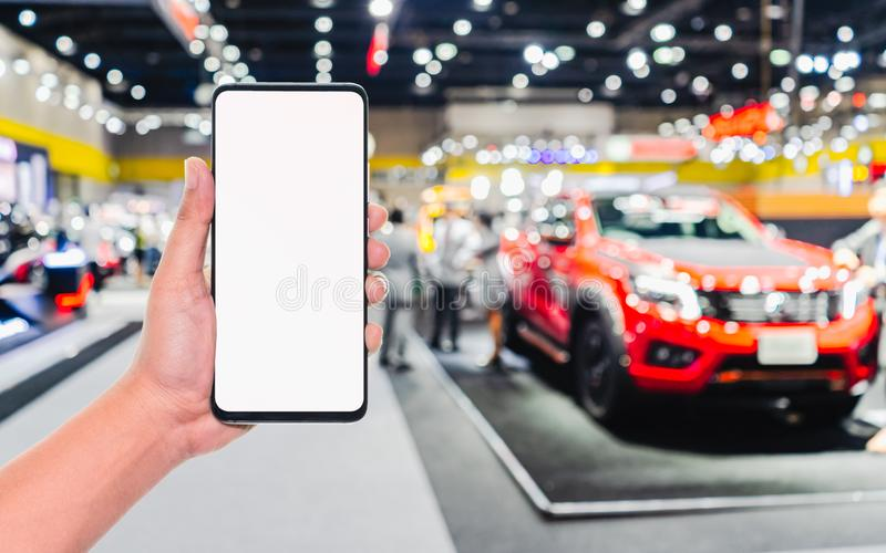 Mock up mobile phone. Hand holding mobile phone with abstract blurred cars exhibition show background image. Car shopping online,. Internet and social network royalty free stock photos