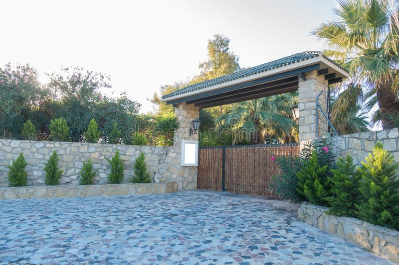 Mock up near the gate to the private house yard. Wooden gates and a high stone fence stock photography