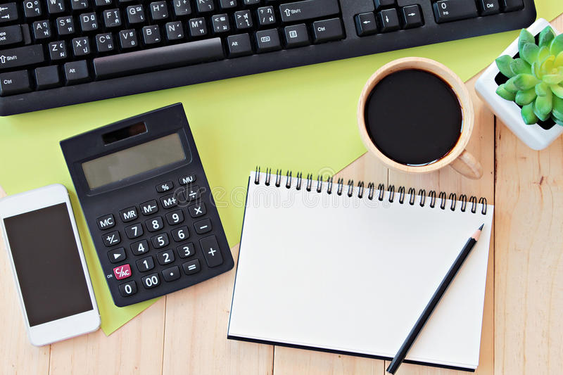 Mock up of office table desk workspace with blank notebook, smart phone, calculator, computer keyboard and coffee royalty free stock images