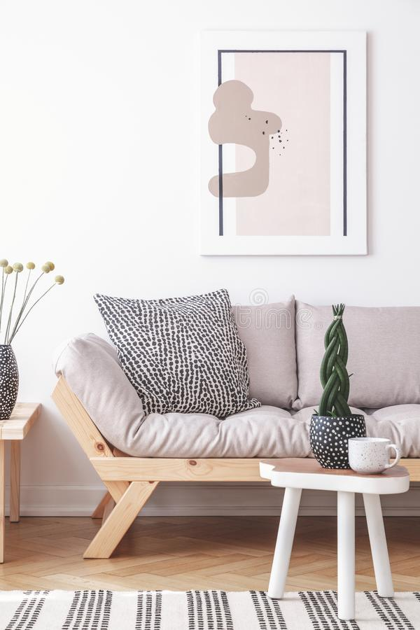 Mock-up painting on a white wall of an artistic living room interior with simple, wooden furniture and patterned decorations. Concept royalty free stock photos