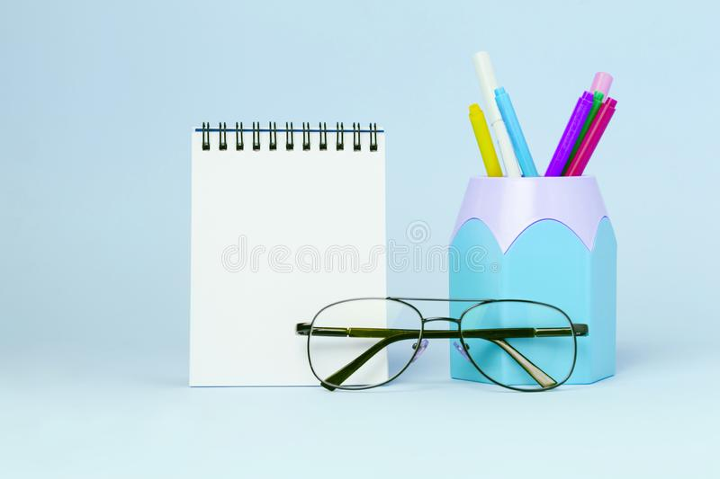 Mock up picture of notebook and office supplies, pencil holder on blue background. stock photography
